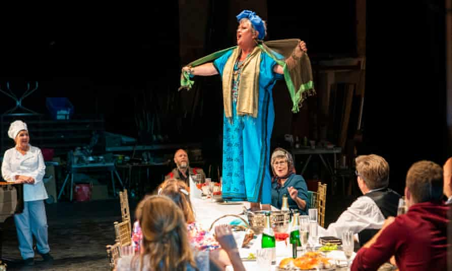 A soprano in costume standing on a dining table singing, while members of the cast seated around the table look on