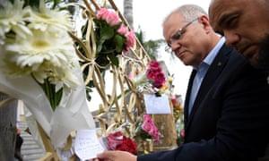 Scott Morrison looks at floral tributes