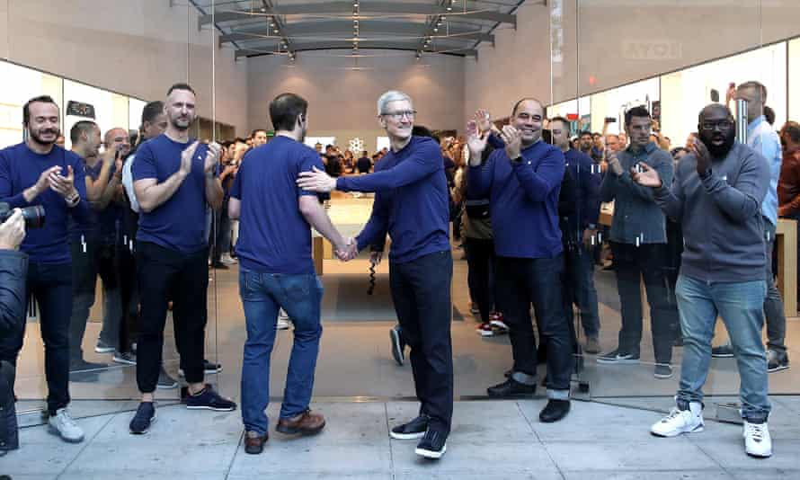 Apple CEO Tim Cook greets customers as the Palo Alto, California, store's employees clap their arrival to purchase the new iPhone X.