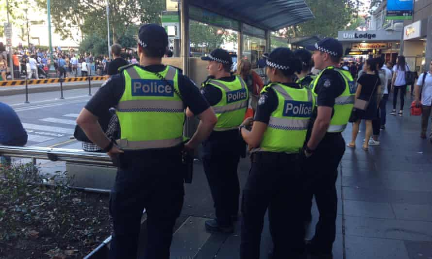 Police watch on as a couple of hundred people rally against Trump at the State Library in Melbourne.