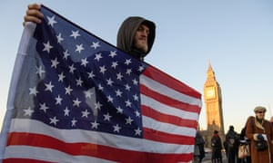 A protester holds a US flag on Westminster Bridge to protest against the inauguration of Donald Trump.