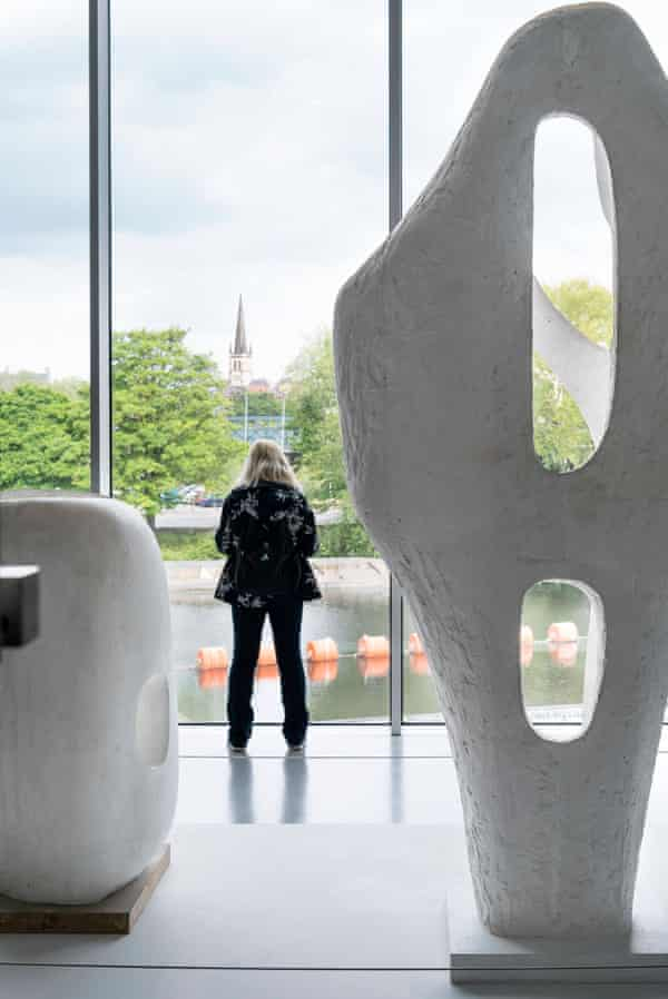 Barbara Hepworth sculptures on display and a woman looking out of a window
