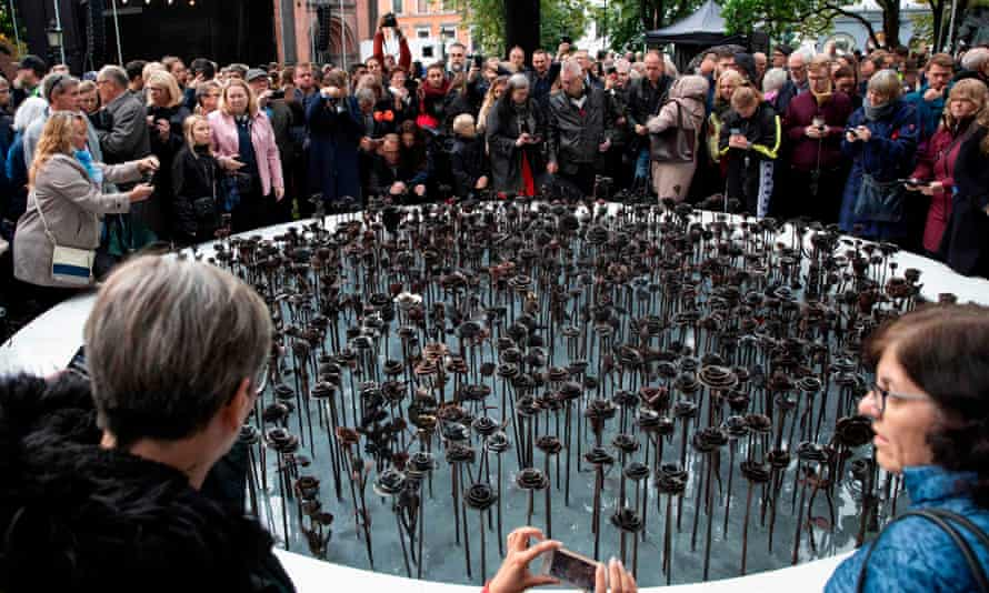 People gather at an 'iron roses' memorial outside Oslo cathedral on the anniversary of the attacks by Anders Breivik.