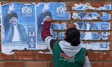 A woman removes posters of Bolivia's Evo Morales from a wall