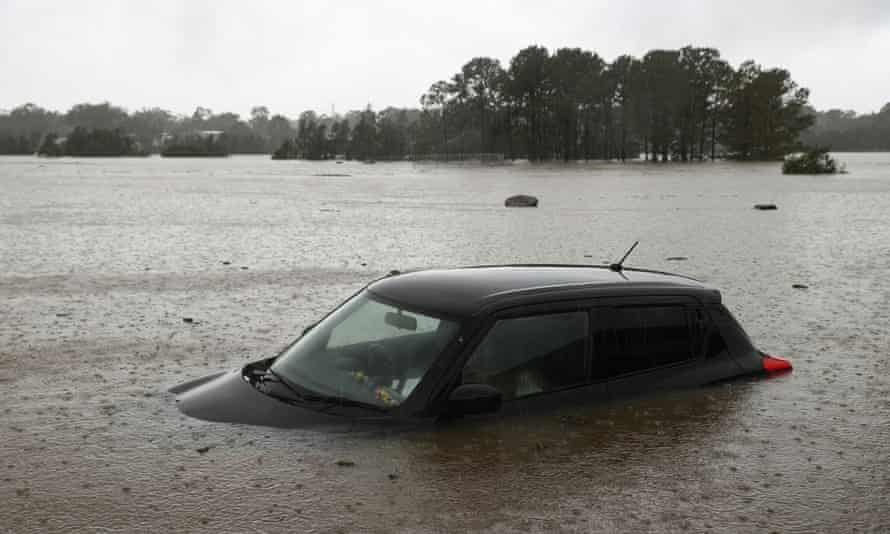A partially submerged car is seen abandoned in floodwaters in the suburb of Windsor as the state of New South Wales experiences widespread flooding and severe weather.