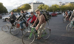 People cycle past the Arc de Triomphe in Paris