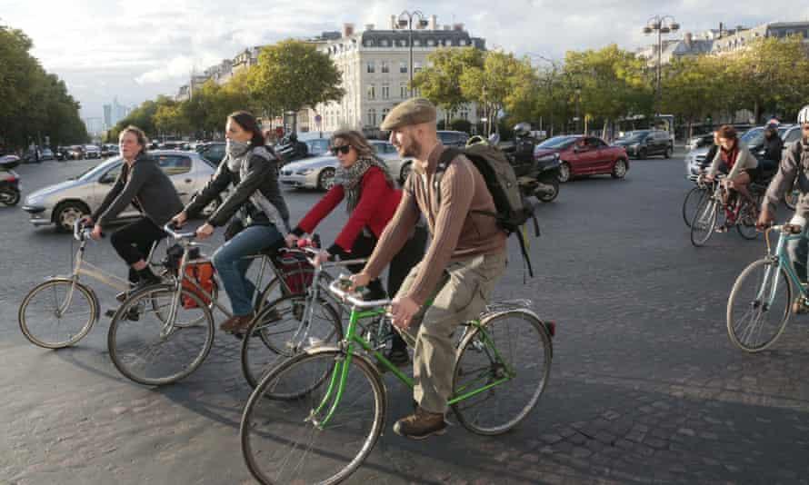 People cycle past the Arc de Triomphe in Paris