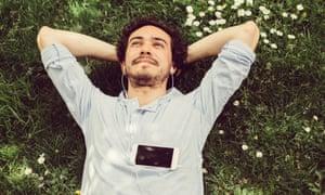 Jeune homme se détendre dans l'herbe et profiter de la musique