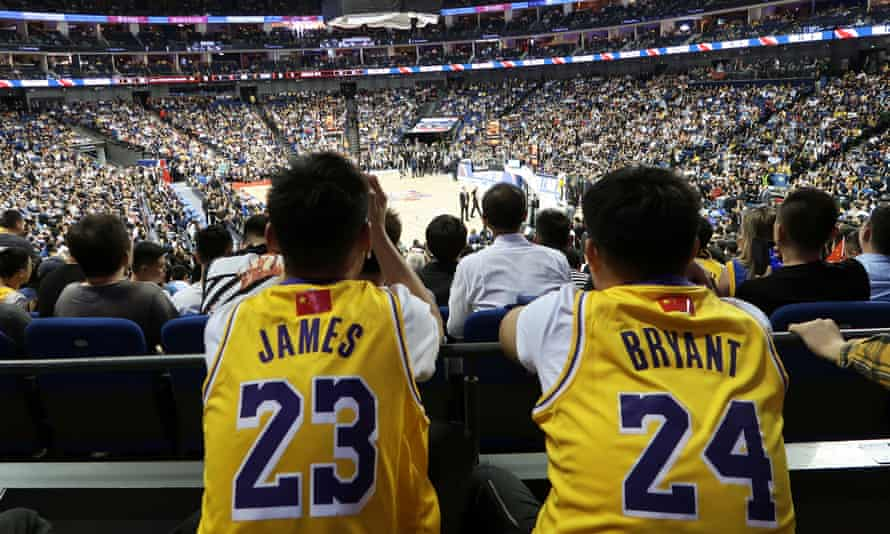 Fans in LeBron James and Kobe Bryant jerseys watch an NBA preseason game in Shanghai