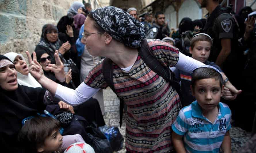 an israeli woman and a palestinian woman gesture at each other at a protest in jerusalems old city