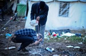 Vučjak camp, Bosnia: a man has his head washed at the migration camp near Bihać