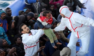 A boy is rescued from a dinghy by Libyan coastguard.