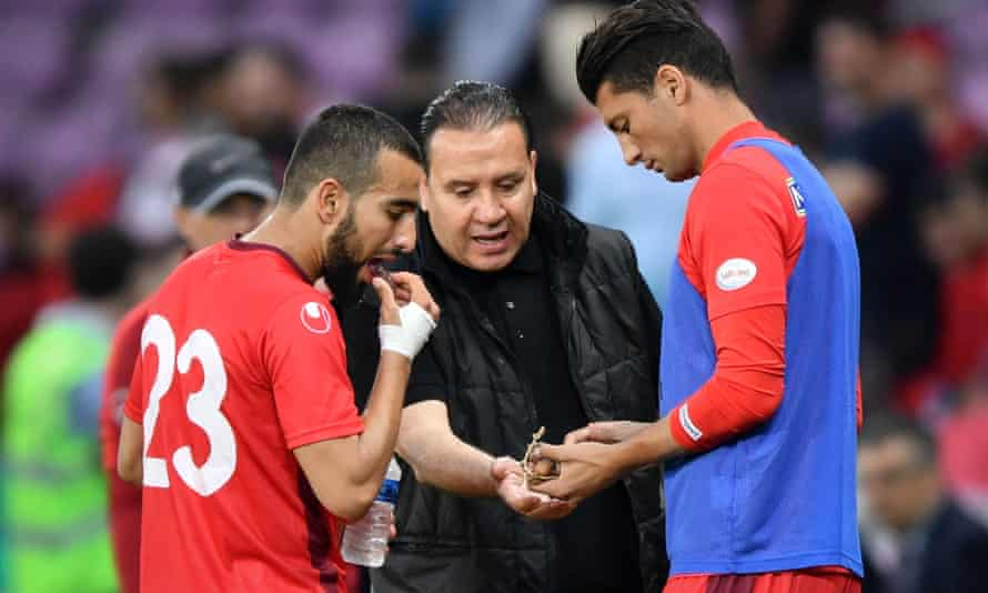 Tunisia's head coach Nabil Maâloul distributes dates to  midfielder Naïm Sliti, left, and defender Rami Bedoui during the friendly with Turkey. Maâloul said he had asked his goalkeeper, Mouez Hassen, to simulate an injury in warm-up games to allow his players to break the fast
