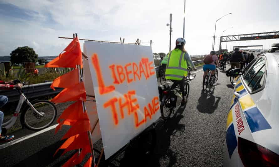 """The """"Liberate the Lane"""" group held a rally at Point Erin Park this morning, calling for a three-month cycle lane trial on the harbour bridge. After the rally hundreds of cyclists broke police lines and rode over the bridge. 30 May 2021 New Zealand Herald photograph by Dean Purcell. NZH 31May21 -"""