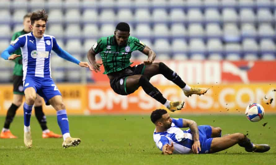 Kwadwo Baah feels the force of a tackle by Wigan's Curtis Tilt.