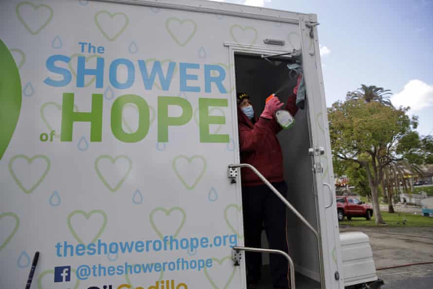 Lisa Marie Nava cleans a mobile shower provided by the Shower of Hope, a homeless services group, in MacArthur Park in Los Angeles on 23 March 2020.