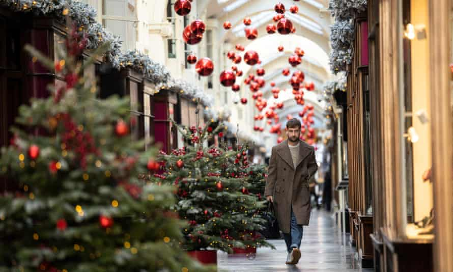 A member of the public walks through a Christmas-decorated Burlington Arcade in London.