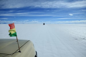 A head-out-of-the-window shot from the passenger seat of a four-wheel drive crossing the Salar de Uyuni salt flats in Bolivia. The flats are pure white, the sky blue with light white cloud.
