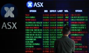 A man stands in front of digital market boards at the Australian Stock Exchange in Sydney, Australia.