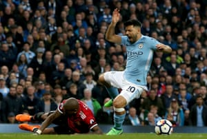 Sergio Aguero is floored by Ashley Young in the box.