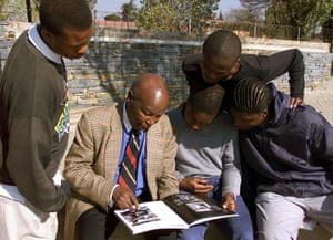 Teenagers look on in 2001 as veteran photojournalist Alf Khumalo, who died in 2012, shows them photographs of a burning building near their Soweto school during the uprising.