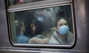 A woman wears a face mask on the subway in New York, New York, on 13 March.