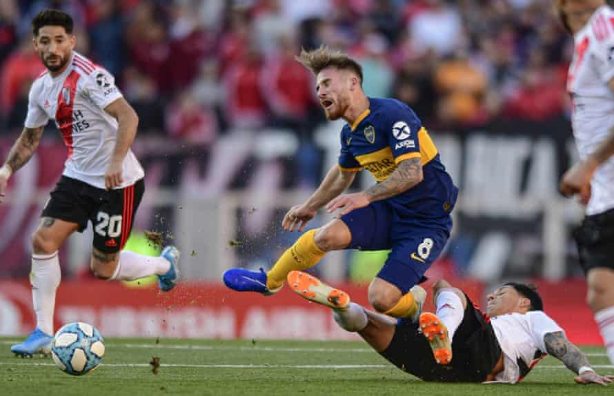 Alexis Mac Allister feels the force of a River Plate tackle while playing for Boca Juniors in September 2019.