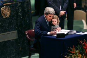 John Kerry, then the US secretary of state, holds his granddaughter while signing the Paris climate accord