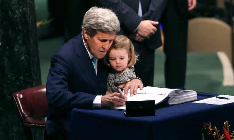 Kerry holds his two year-old granddaughter for the signing of the 2016 Paris climate agreement.