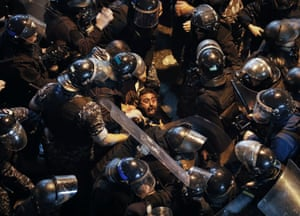 Beirut, Lebanon: riot police arrest an anti-government demonstrator who was outside the police headquarters demanding the release of those taken into custody during the previous night