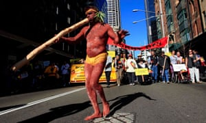 An Indigenous Australian man leads a march through Sydney to mark the anniversary of the Aboriginal referendum.