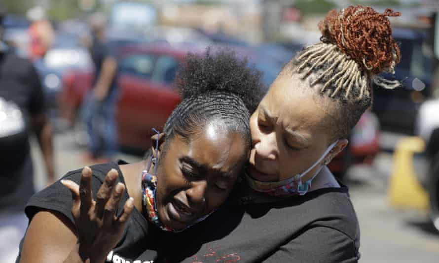 Two women pray on Tuesday in Louisville, Kentucky, near the intersection where David McAtee was killed.