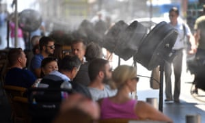 Fans spray water on customers on the terrace of a bar in Madrid