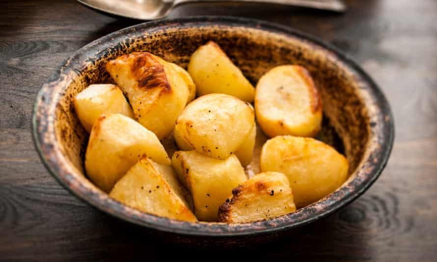Bowl of roast potatoesRustic metal bowl of roast potatoes on a wooden table.