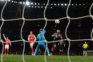 Arturo Vidal chips the ball past Arsenal keeper David Ospina to score Bayern Munich's fourth goal.