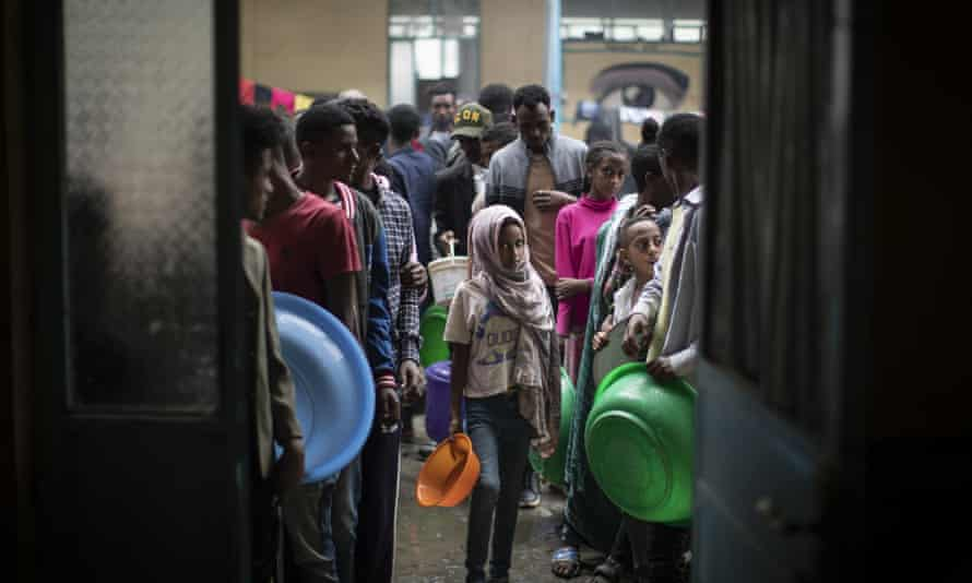 Displaced people queue to receive food at a school that has become a makeshift home to thousands who have fled the conflict, in Mekele, Tigray.