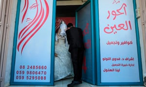 Palestinian groom Ahmed Omar Khallah takes his veiled bride from a beauty salon in the northern Gaza Strip.