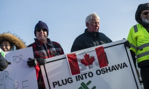 Activists hold signs outside the General Motors plant in Oshawa, Ontario, on the final day of production on 18 December.