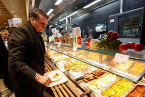 Handout picture released by the Brazilian presidency showing Brazilian President Jair Bolsonaro serving his lunch at a Migros supermarket restaurant in Davos, Switzerland, after speaking at the World Economic Forum on January 22, 2019.