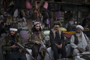 Taliban fighters sit next to street vendors at a local market in Kabul.