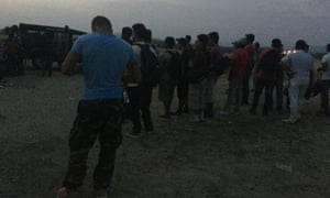 Migrants standing at the invisible border between Greece and Macedonia, where soldiers prevent them from going further.