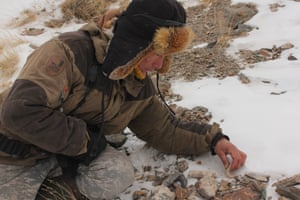 The lead tracker and wolf hunter Valery Orgunov examines potential snow leopard excrement.