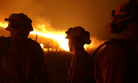 Incarcerated firefighters stand guard as flames from the Butte fire approach a containment line near San Andreas, California, in 2015.