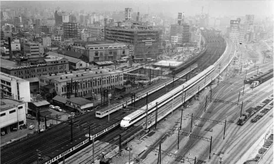 A shinkansen bullet train runs toward Tokyo Station past Shiodome Freight Terminal during a test run on in July 1964.