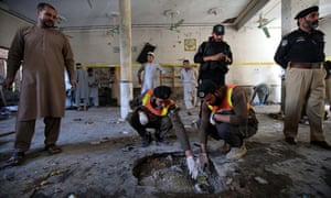 Security officials inspect a crater at the site of the blast at a religious school in Peshawar.