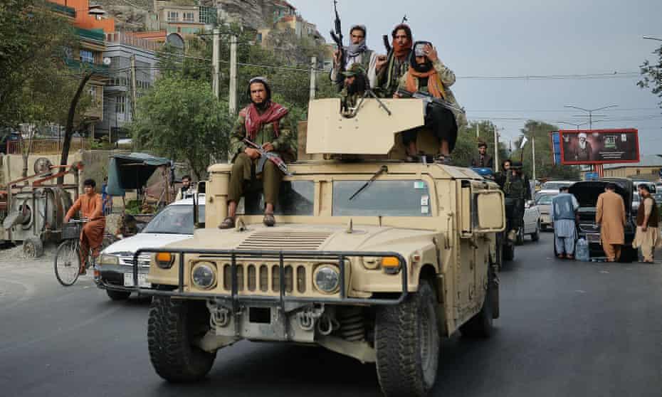 Taliban fighters atop a Humvee vehicle celebrate the departure of US troops this week.