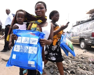 A woman carrying a baby holds a treated mosquito net during a malaria prevention action at Ajah in Eti Osa, a district of Lagos, Nigeria