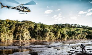 A police helicopter hovers over the Parque de Cachoeira community in Minas Gerais as Afonso Ferreira, 20, points out the leg of a missing person in the mud.