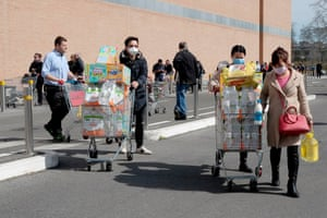 People with face masks stock up on food and other goods in Rome