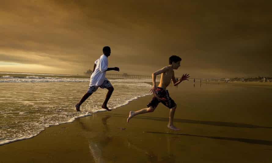 Two boys run near Huntington Beach pier.